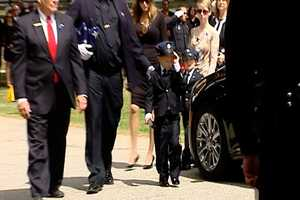 Officer Jacobs's children in uniform and wife as they leave his funeral funeral