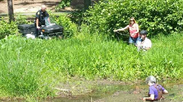 A woman and her dog had to be rescued by Furman University police Wednesday after they got stuck in the mud.