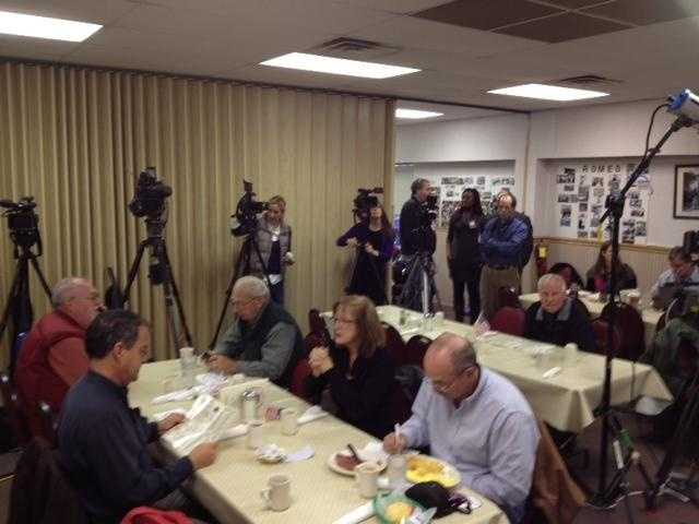 A dozen different media outlets have lined up in one area in the cafeteria.