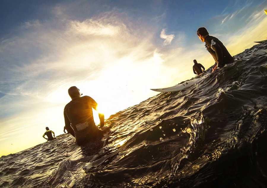 Calm before the storm: surfers watch the sunrise during warm-up sessions Sunday morning.