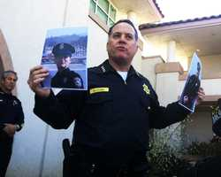 Vogel holds up photos of the fallen officers. They were slain while investigating a man who officials said was an imminent and dangerous threat to the Santa Cruz community on Feb. 26, 2013.
