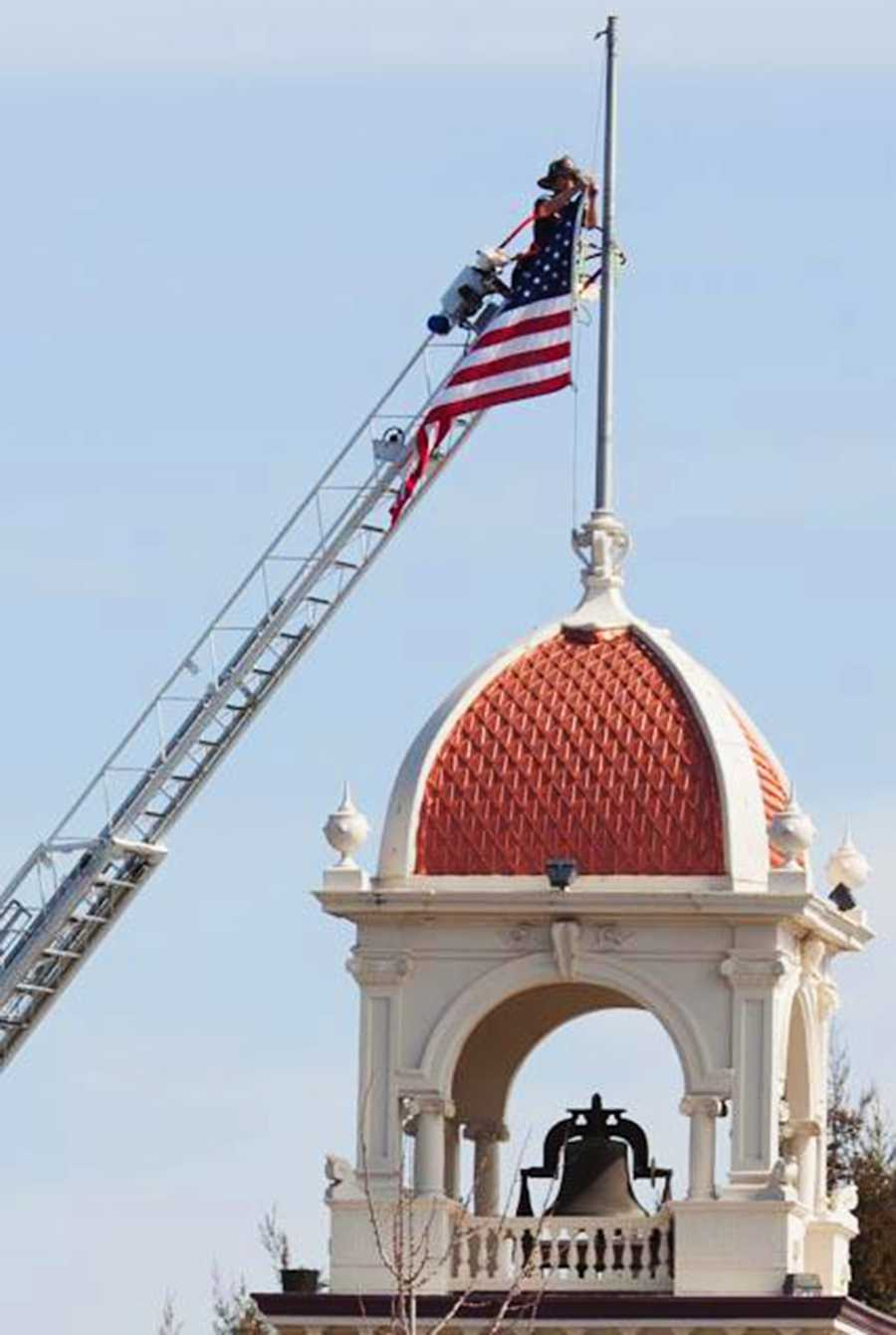 A Santa Cruz firefighter lowers a U.S. flag on top of a clock tower on Pacific Avenue to mourn the slain detectives. (Feb. 27, 2013)