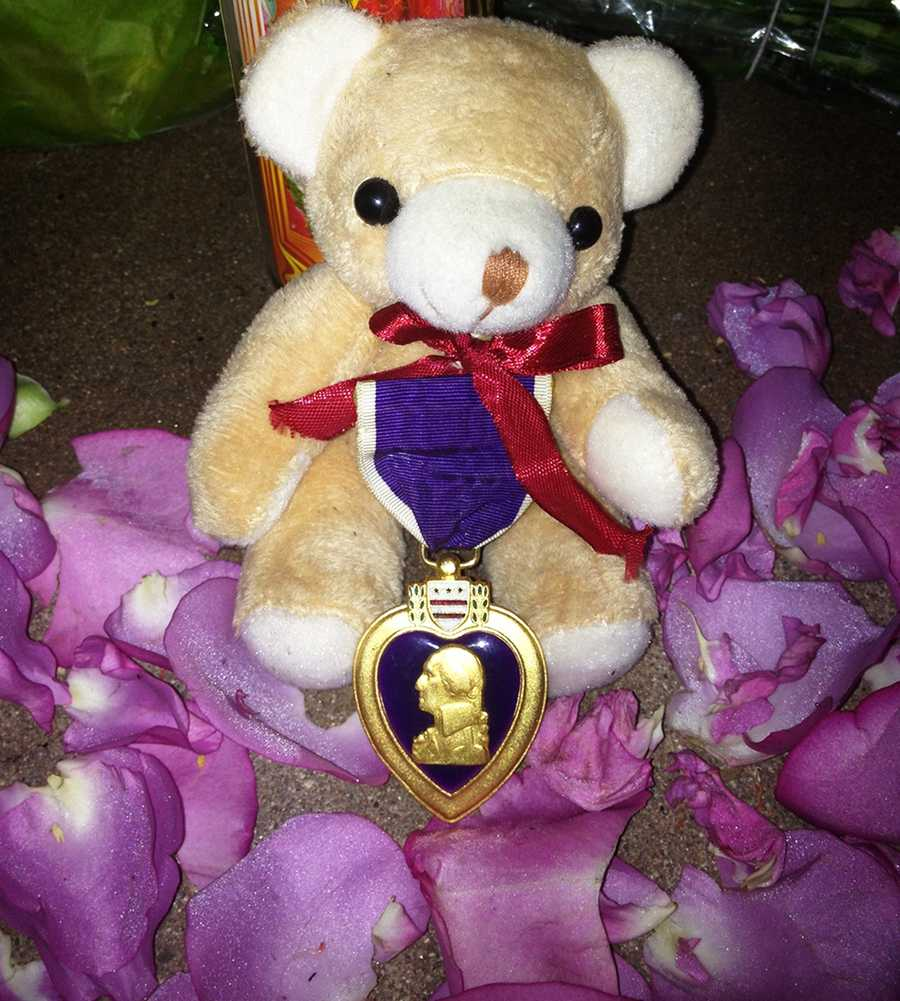 "An unknown solider left a Purple Heart medal pinned to a teddy bear as a tribute to two Santa Cruz police detectives killed in the line of duty. Santa Cruz police found the teddy bear with purple orchid flower petals circling it.An anonymous message found along with the gift read:""The teddy bear reflects the love of our community for the police and all the work they endure during their shifts, the red ribbon reflects the precious blood shed in the line of duty, the Purple Heart is for the sacrifice above and beyond the call of duty, when one loses their life for the protection of others and the greater good. I know you will understand."""