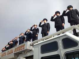 Firefighters salute in Los Gatos as a memorial procession passes on Highway 17.