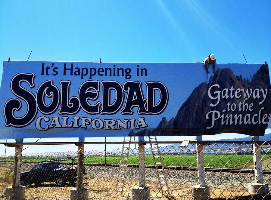 "In an unexpected moment, when Soledad's new sign was raised into the sky above Highway 101 Wednesday afternoon, its large font proclaimed, ""It's Happening in Soledad,"" a slogan that the city council had voted to get rid of.  (May 29, 2013)"