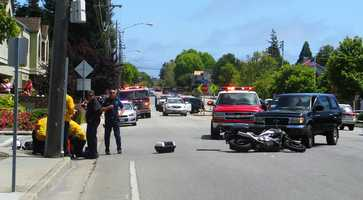 (June 3, 2014) A woman was walking across Bay Avenue at Hill Street in Capitola when she was hit by an SUV. A few minutes later, a black pickup truck hit the motorcycle cop.