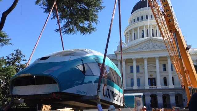 A crane unloads a high-speed rail model at the state Capitol in Sacramento.