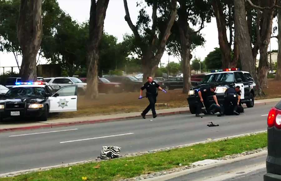 The officer under the most intense scrutiny is the one with purple gloves on the left. He ran out of a patrol car and used a baton after Velasco had already been hit many times and was on the ground.