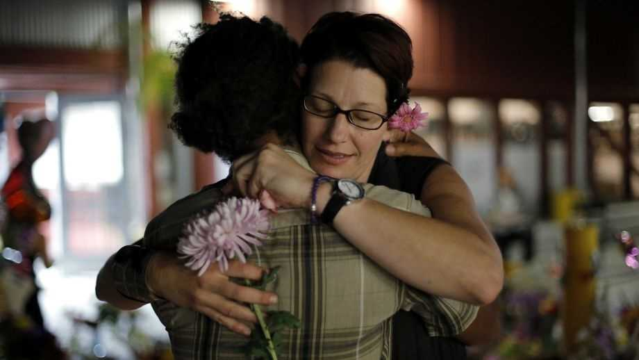 Laura Jordan hugs Elijah Pfotenhauer in front of Madyson Jordan Middleton's memorial at the Tannery Arts Center in Santa Cruz, on Saturday, Aug. 1, 2015.