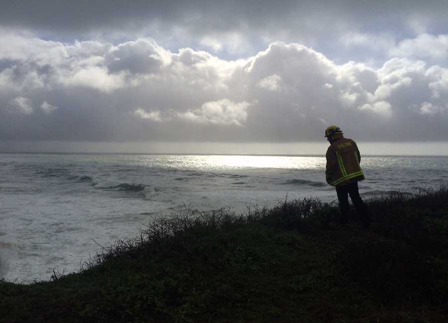 A firefighter searches for two UC Santa Cruz students who were swept out to sea by big waves at Bonny Doon Beach on Jan. 18.