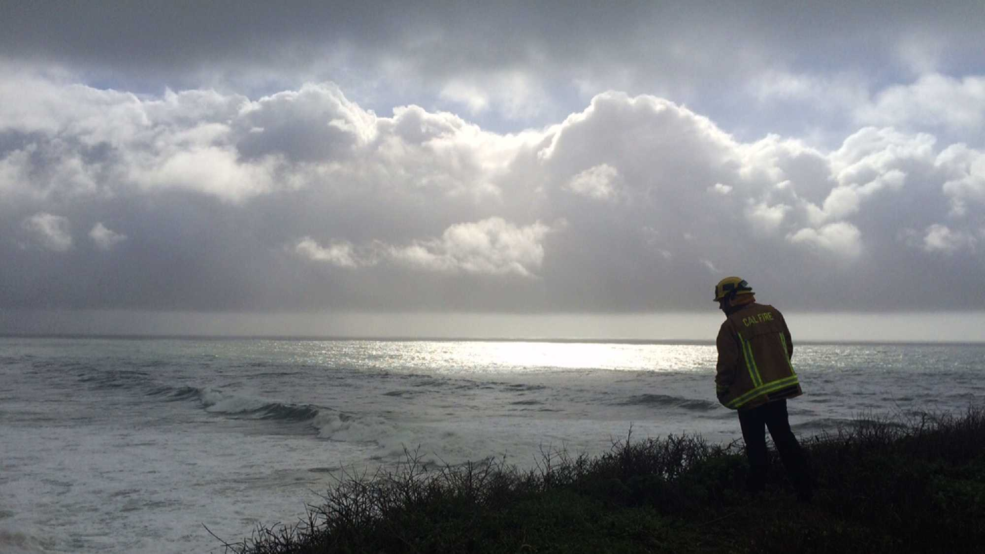 A firefighter searches for two people who were swept out to sea by big waves at Bonny Doon Beach.  (Jan. 19, 2016)