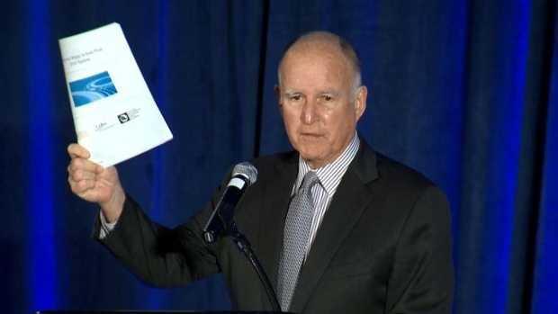 Gov. Jerry Brown holds a copy of the California Water Action Plan 2016 update.