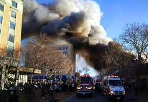 Crowds of onlookers gathered to watch a giant plume of black smoke rise into a bright blue sky, and flames flicker through the historic building's windows.
