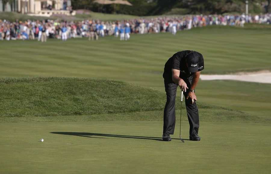 With a chance to force a playoff at the AT&T Pebble Beach Pro-Am, Phil Mickelson misses his birdie putt on the 18th hole.