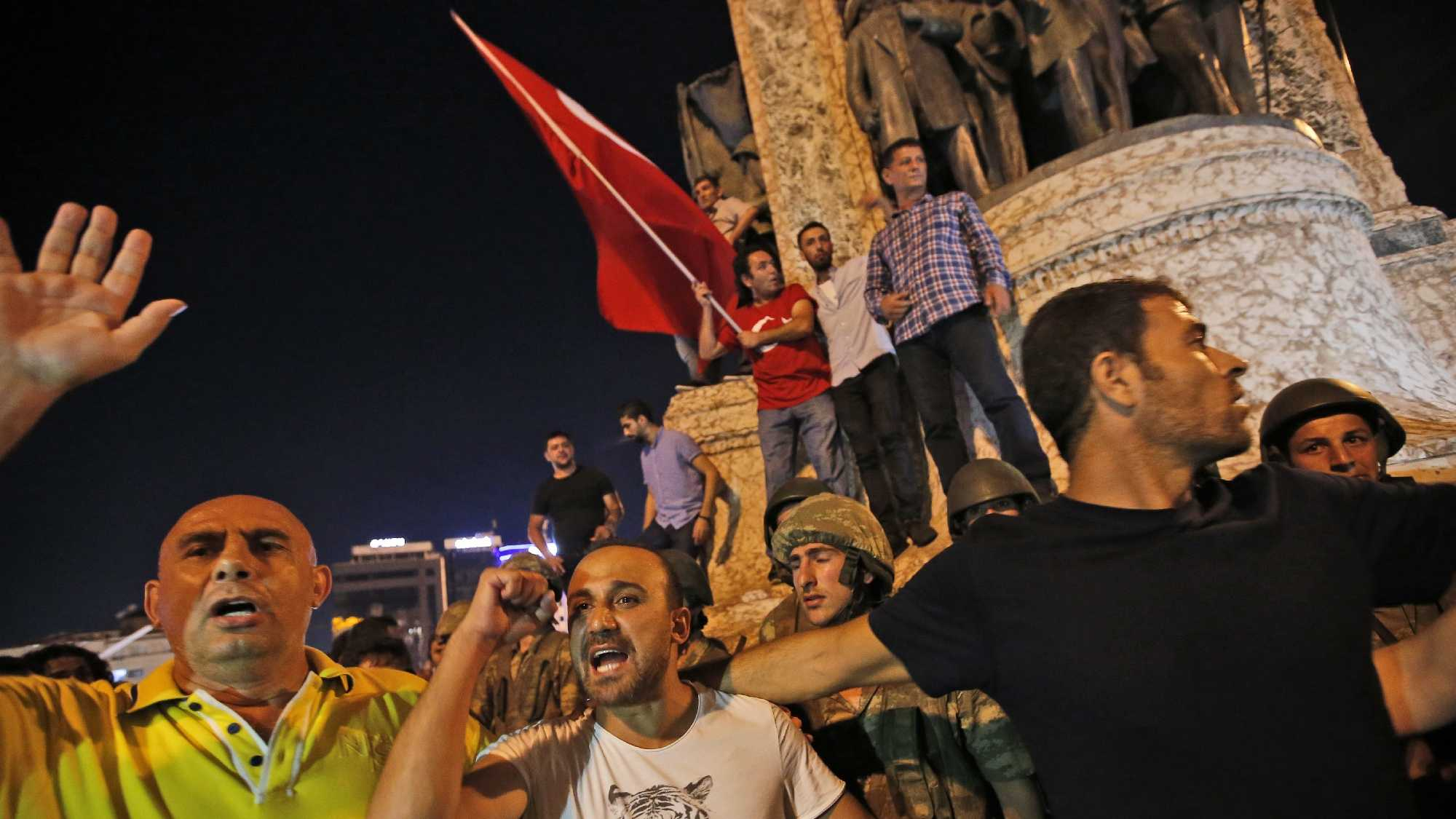 Supporters of Turkey's President Recep Tayyip Erdogan, protest in front of soldiers in Istanbul's Taksim square, early Saturday. Turkey's prime minister says a group within Turkey's military has engaged in what appeared to be an attempted coup.