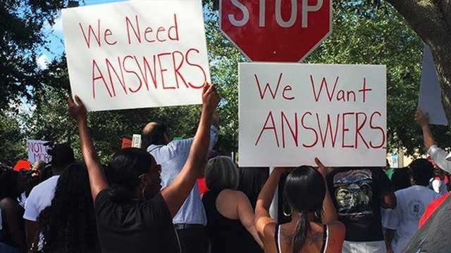 "Oct. 22: Supporters raise signs that read ""We need answers."" A sentiment echoed throughout the rally by various speakers."