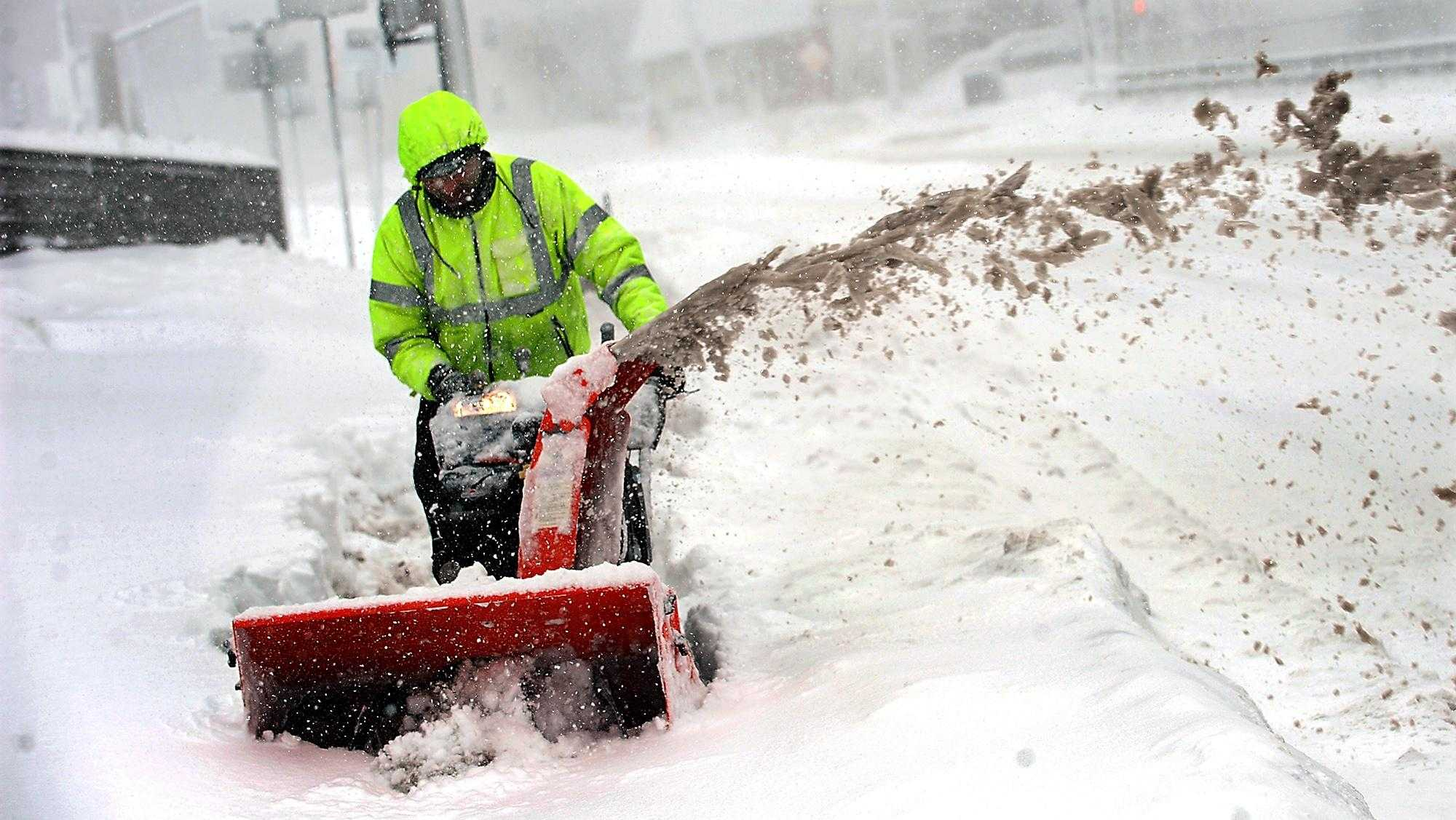 A worker from Maple and Clover Landscaping in Framingham struggles to clear snow at 5 Egell Road in Framingham Centre during Tuesday's nor'easter.