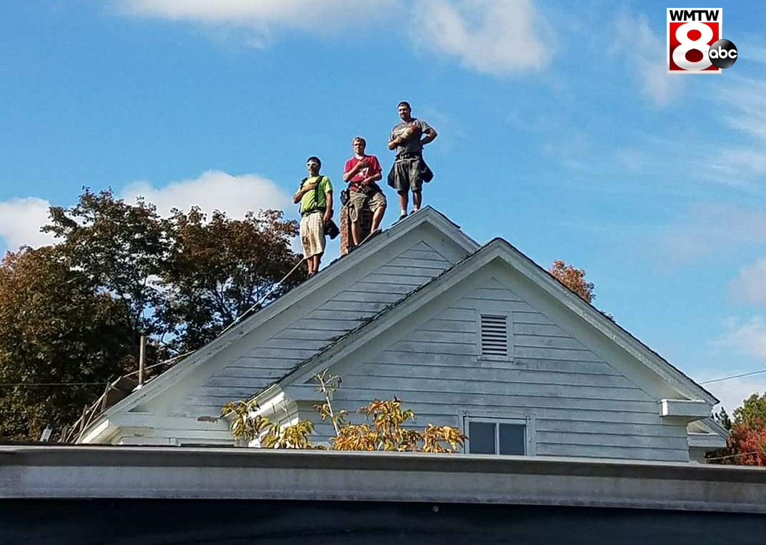 Roofers halt work to stand for nearby school's national anthem