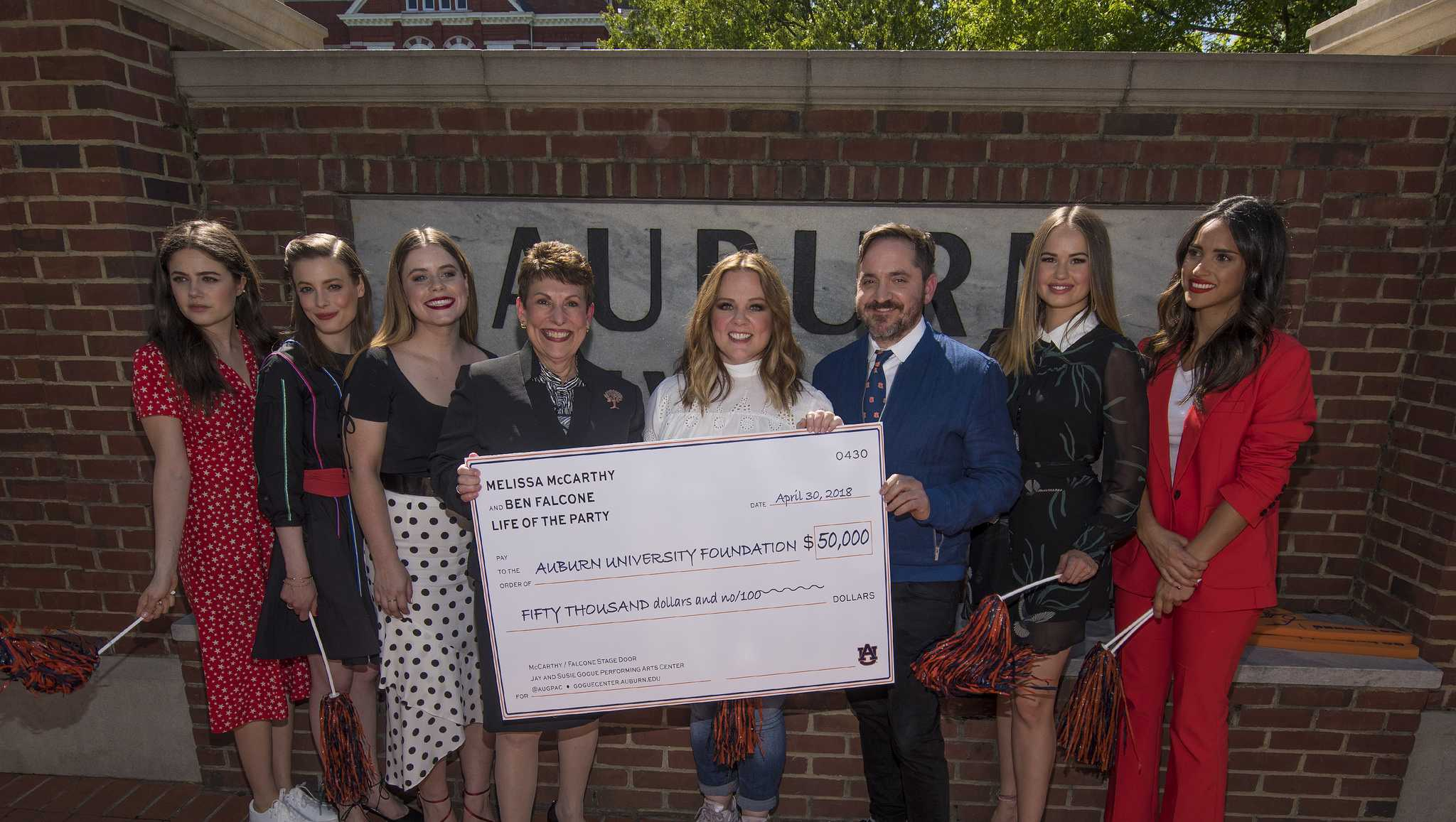 """Melissa McCarthy, center, and her husband Ben Falcone presented Auburn University with a check for $50,000 for the Jay and Susie Gogue Performing Arts Center. Pictured, from left, are Molly Gordon, Gillian Jacobs, Jessie Ennis, Vice President of Development and President of the Auburn University Foundation Jane DiFolco Parker, McCarthy, Falcone, Debby Ryan and Adria Arjona. The actors were in Lee County April 30 for the premiere of """"Life of the Party."""""""