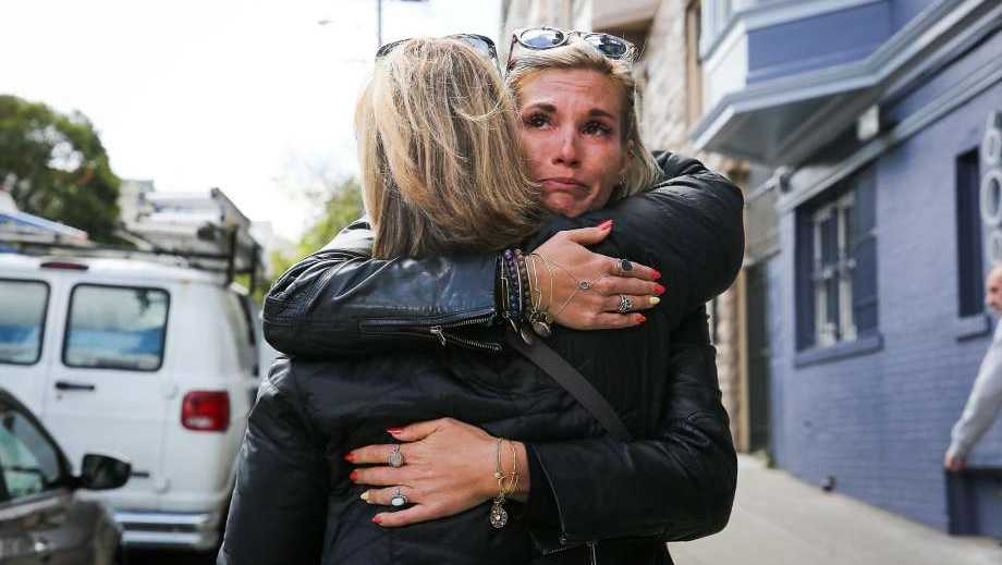 Julia Wilkinson (back), of Charlotte, North Carolina, hugs her mother Mary Wilkinson (front) a day after her father's ashes were stolen from their rental car on Wednesday afternoon.
