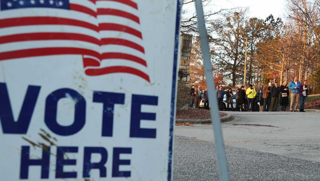 Voters wait in line to cast their ballot at a polling station.