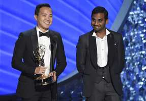 "Kelvin Yu, left, and Aziz Ansari accept the award for outstanding writing for a comedy series for ""Master of None"" at the 68th Primetime Emmy Awards on Sunday, Sept. 18, 2016, at the Microsoft Theater in Los Angeles."