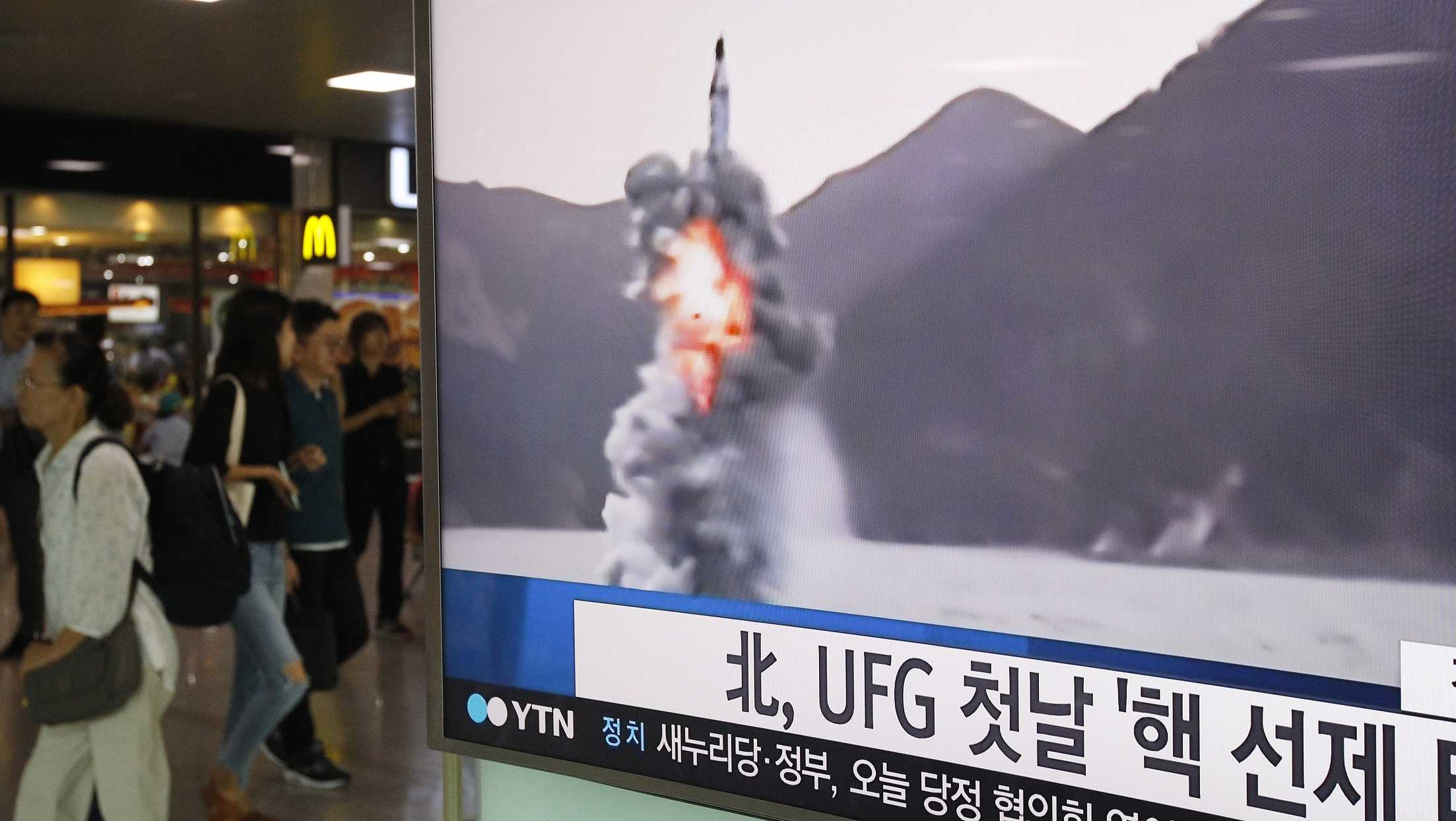 "People pass by a TV news program showing a file footage of North Korea's ballistic missile that the North claimed to have launched from underwater, at Seoul Railway station in Seoul, South Korea, Wednesday, Aug. 24, 2016. North Korea on Wednesday fired a ballistic missile from a submarine into the sea in an apparent protest against the start of annual South Korea-U.S. military drills, Seoul's military said. The letters read ""North Korea fired a missile during UFG, Ulchi Freedom Guardian."""