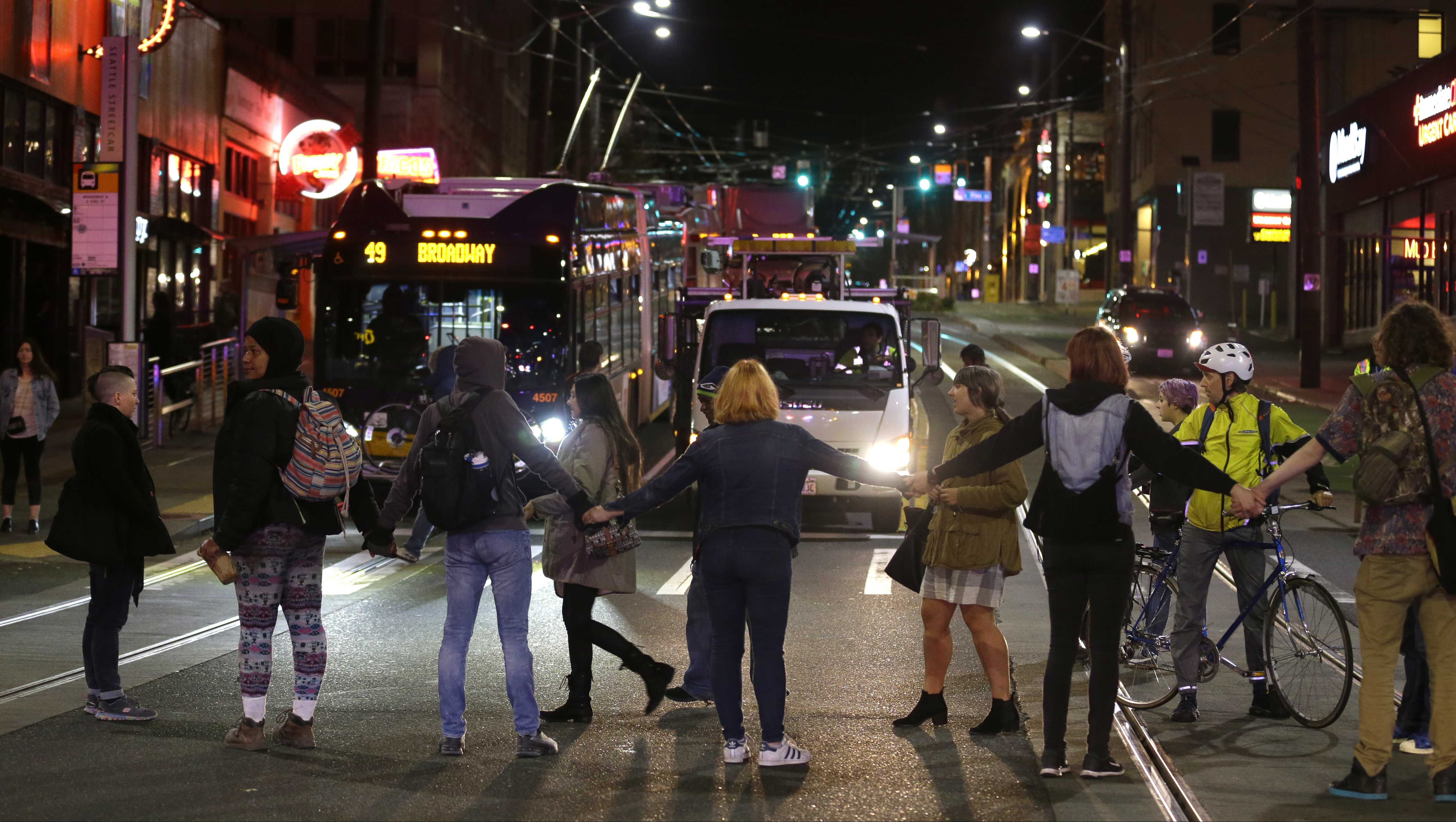 Elsewhere, protesters block a street and stop traffic during a demonstration against President-elect Donald Trump, early Wednesday, Nov. 9, 2016, in Seattle's Capitol Hill neighborhood.