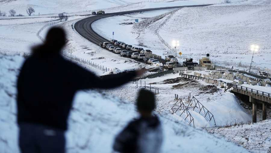 Law enforcement vehicles line a road leading to a blocked bridge next to the Oceti Sakowin camp where people have gathered to protest the Dakota Access oil pipeline in Cannon Ball, N.D., Saturday, Dec. 3, 2016. (AP Photo/David Goldman)