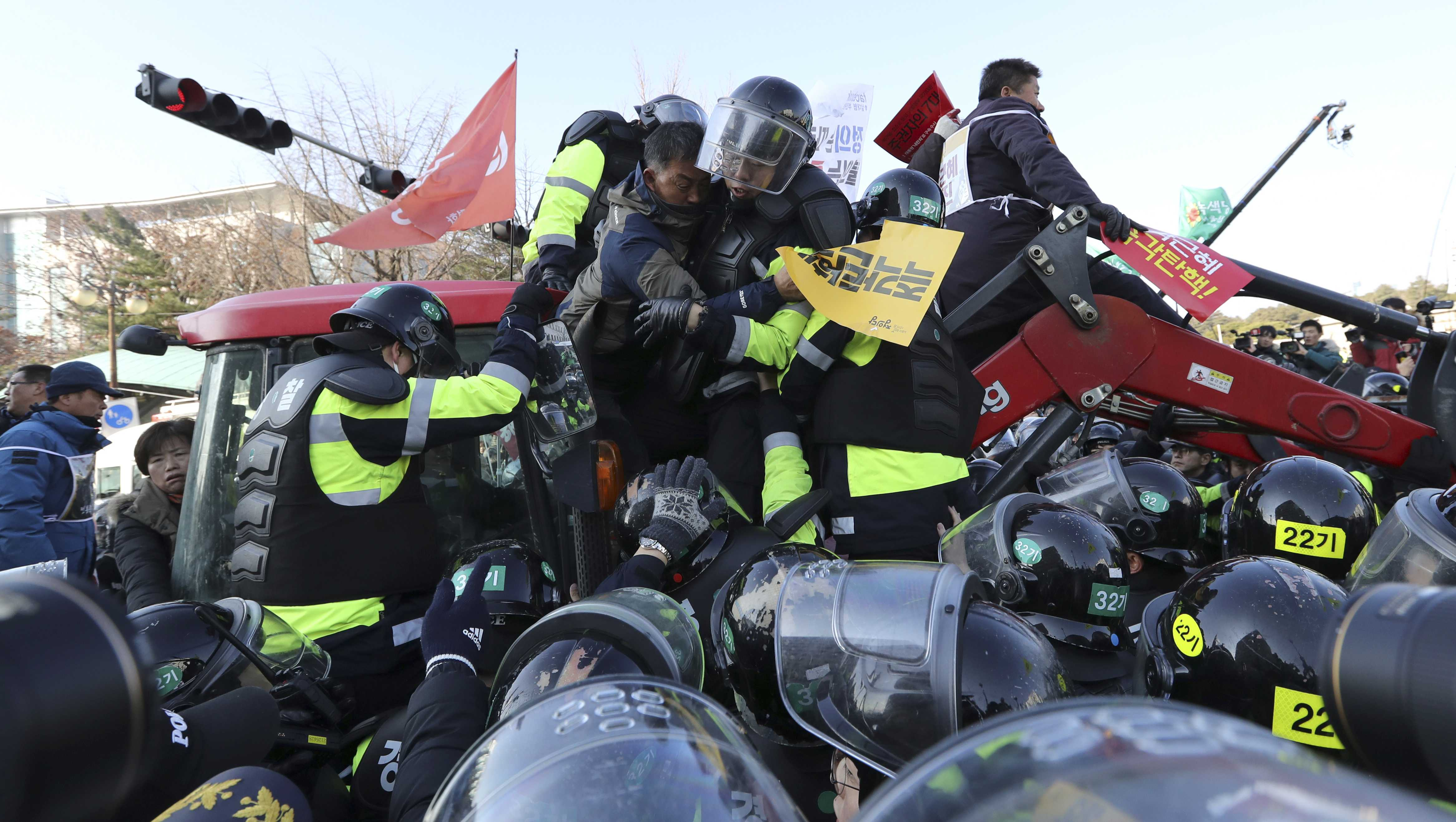 "Police officers try to drag down a protesting farmer from a tractor as they are blocked by police officers before a rally demanding the impeachment of South Korean President Park Geun-hye in front of the National Assembly in Seoul, South Korea, Friday, Dec. 9, 2016. Park entered what could be her last day in power Friday, as lawmakers geared up for what's widely expected to be a successful impeachment vote amid a corruption scandal that has left her isolated and loathed. The banner held by a farmer reads: ""Park Geun-hye, impeachment."""