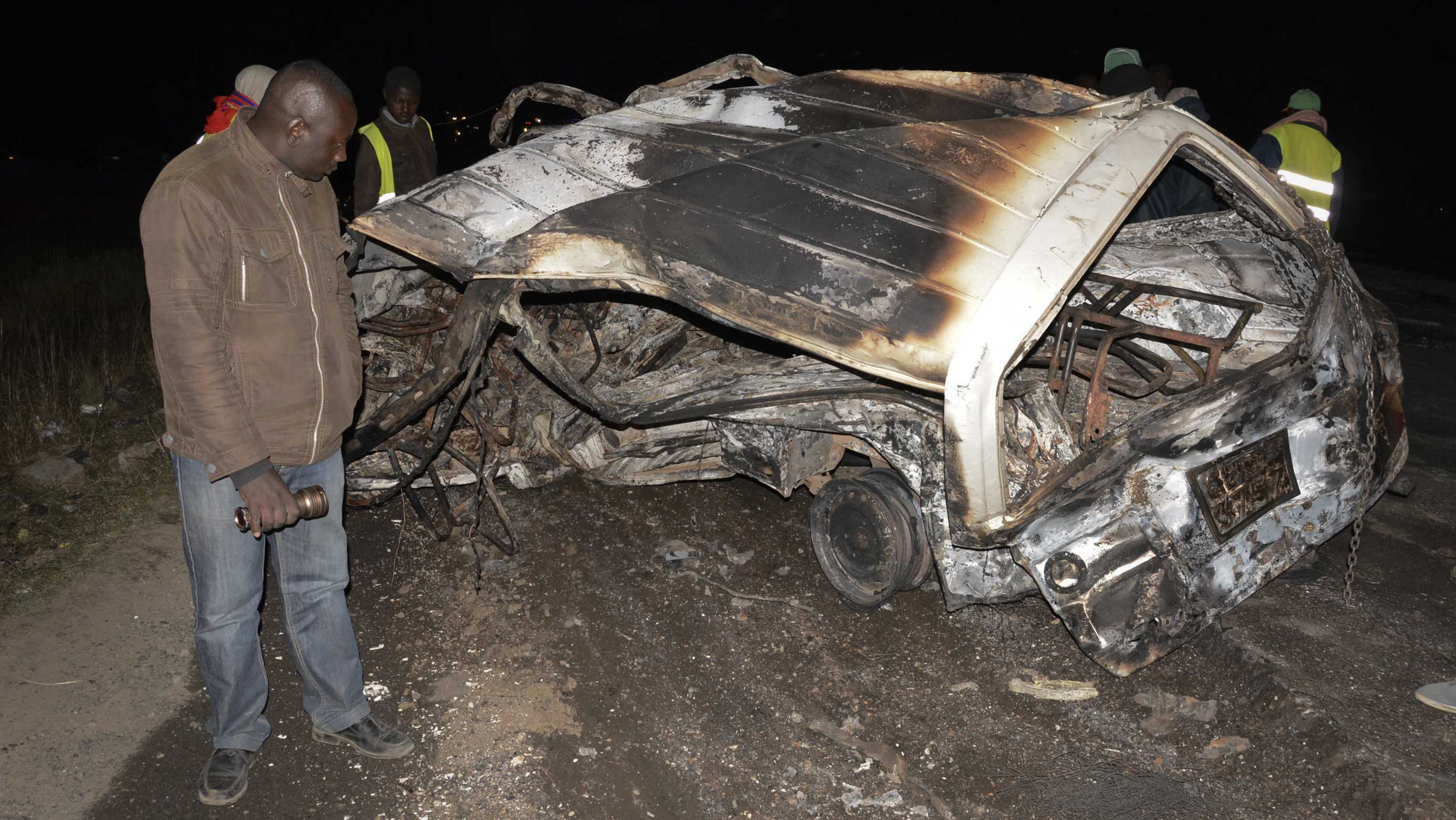 A man looks at the wreckage of a passenger minibus following an accident near Naivasha, Kenya Sunday, Dec. 11, 2017. A tanker carrying chemical gas slammed into other vehicles and burst into flames on a major road in Kenya, officials said Sunday.