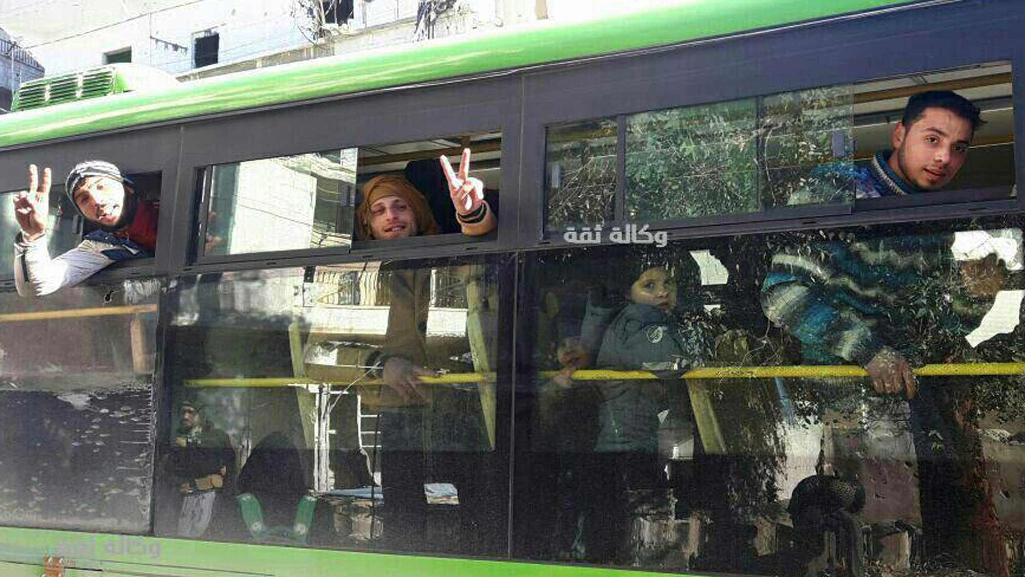 This image released by the Thiqa News Agency, shows civilians, some flashing victory signs, inside a bus that is evacuating people from eastern Aleppo, Syria, Thursday, Dec. 15, 2016.