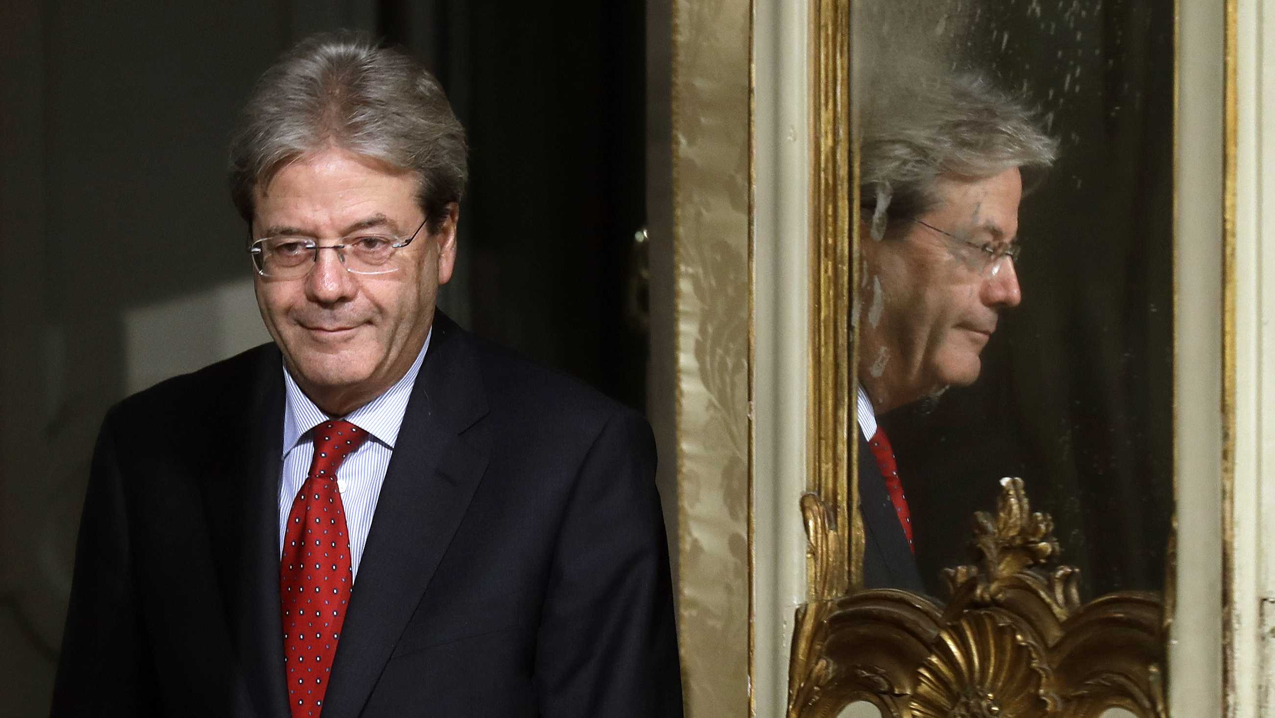 Italian Premier Paolo Gentiloni is mirrored at right as he arrives with Colombian President Juan Manuel Santos to give a press conference following their meeting at Chigi Palace, in Rome, Friday, Dec. 16, 2016.