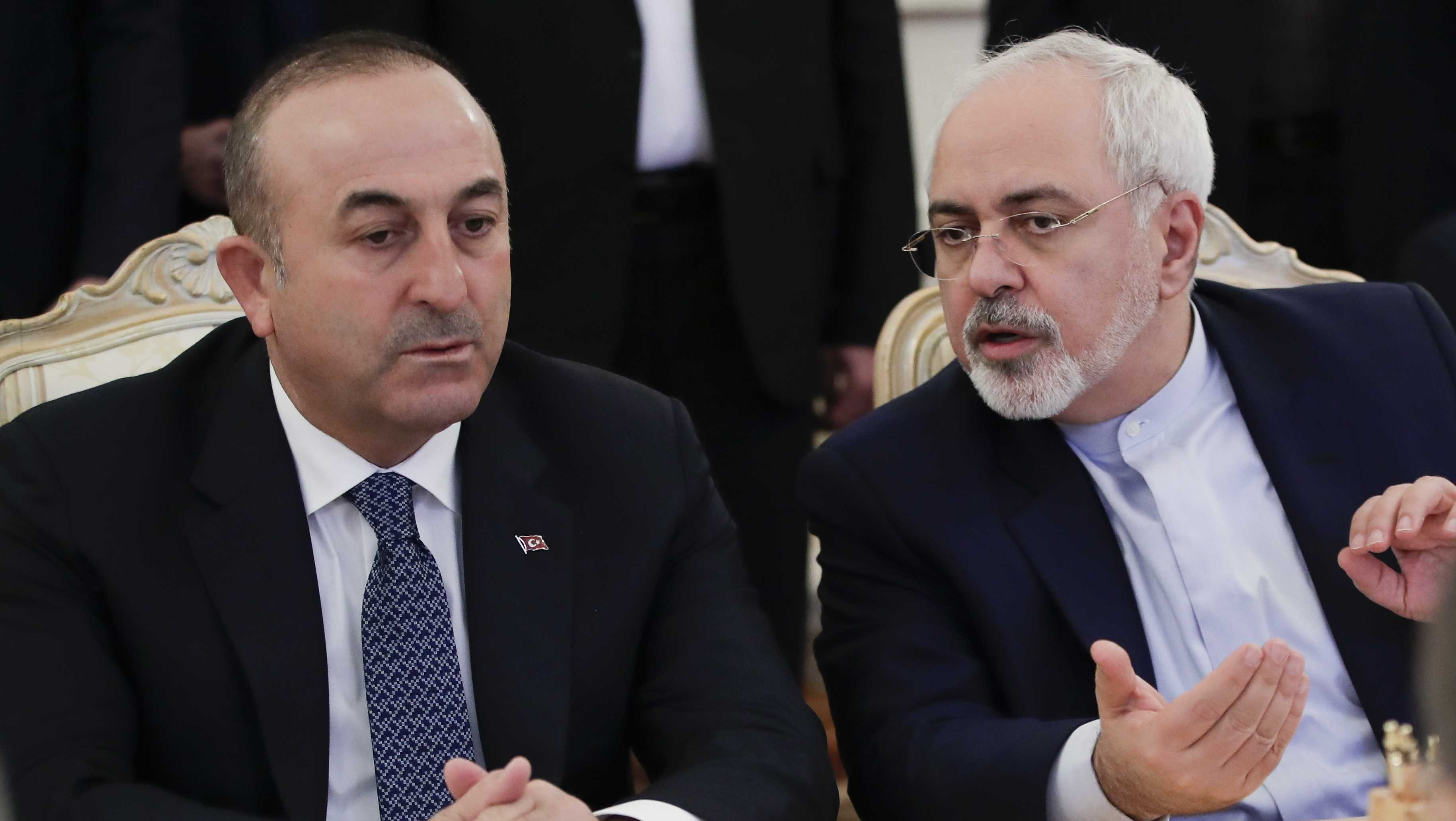 Turkey's Foreign Minister Mevlut Cavusoglu, left, and Iranian Foreign Minister Mohammad Javad Zarif talk to each other during their talks with Russian Foreign Minister Sergey Lavrov in Moscow, Russia, Tuesday, Dec. 20, 2016.