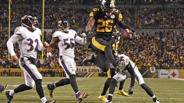 Le'Veon Bell leaps into the end zone ahead of Baltimore Ravens strong safety Eric Weddle for a touchdown