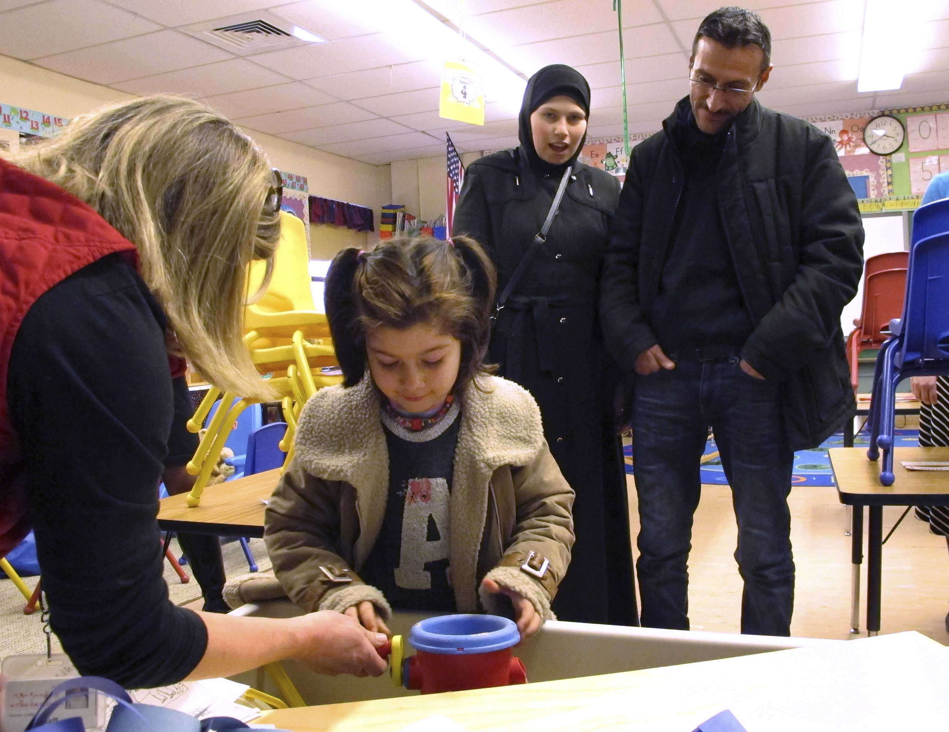 Kindergarten teacher Susan Cody shows newly arrived Syrian refugee Dania Khatib, 5, around a classroom
