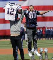 New England Patriots tight End Rob Gronkowski jumps to take quarterback Tom Brady's recovered Super Bowl jersey as he jokes around during baseball Boston Red Sox Home Opening Day ceremonies at Fenway Park, Monday, April 3, 2017, in Boston. The Red Sox face the Pittsburgh Pirates.