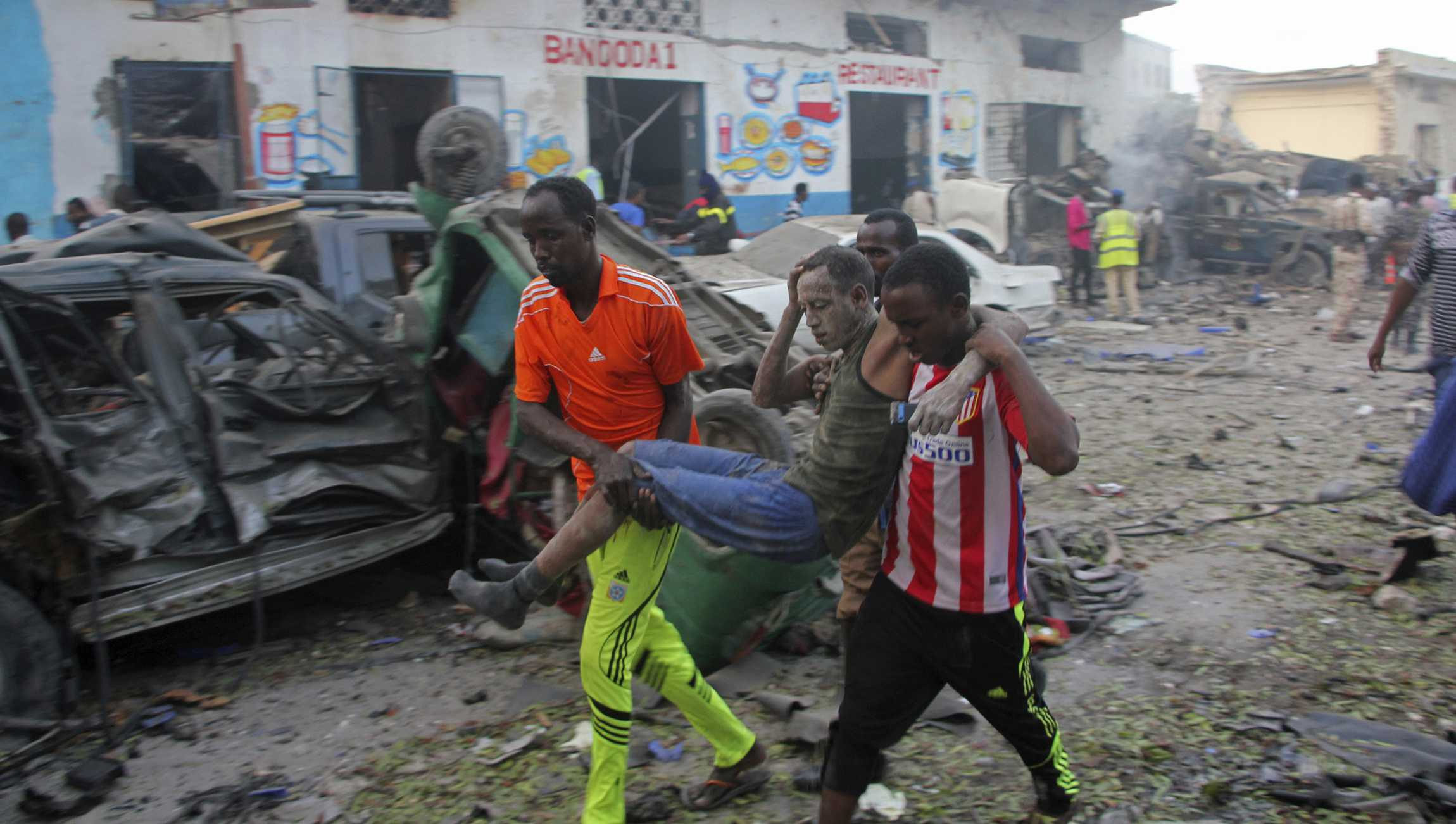 Somalis carry away a man injured after a car bomb was detonated in Mogadishu, Somalia Saturday, Oct 28, 2017. A suicide car bomb exploded outside a popular hotel in Somalia's capital on Saturday, killing at least 10 people and wounding more than 11, while gunfire could be heard inside, police said. A second blast was heard in the area minutes later.