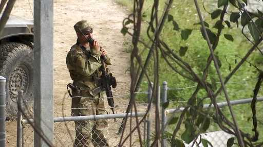 In this April 10, 2018 frame from video, a National Guard troop watches over Rio Grande River on the border in Roma, Texas.