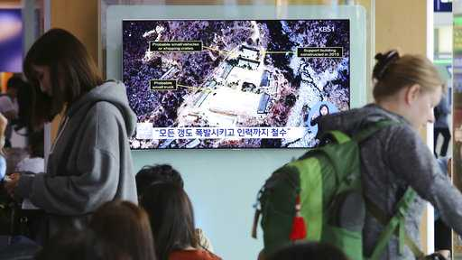 "A TV screen shows a satellite image of the Punggye-ri nuclear test site in North Korea during a news program at the Seoul Railway Station in Seoul, South Korea, Sunday, May 13, 2018. The signs read: ""Explode all tunnels."""
