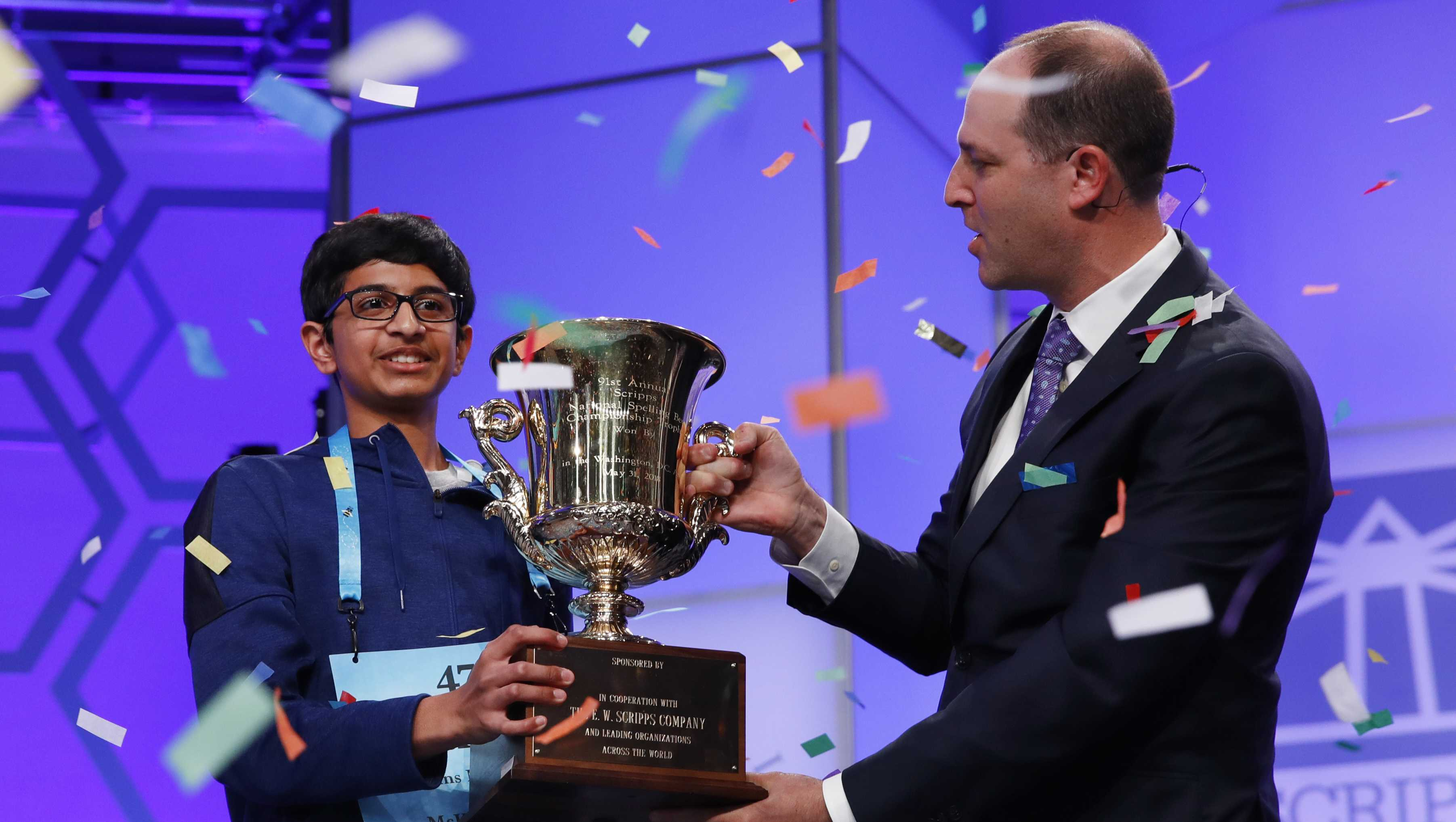 Karthik Nemmani, 14, from McKinney, Texas, left, holds his trophy with President and CEO of the E.W. Scripps Company Adam Symson as confetti falls after winning the Scripps National Spelling Bee in Oxon Hill, Md., Thursday, May 31, 2018.