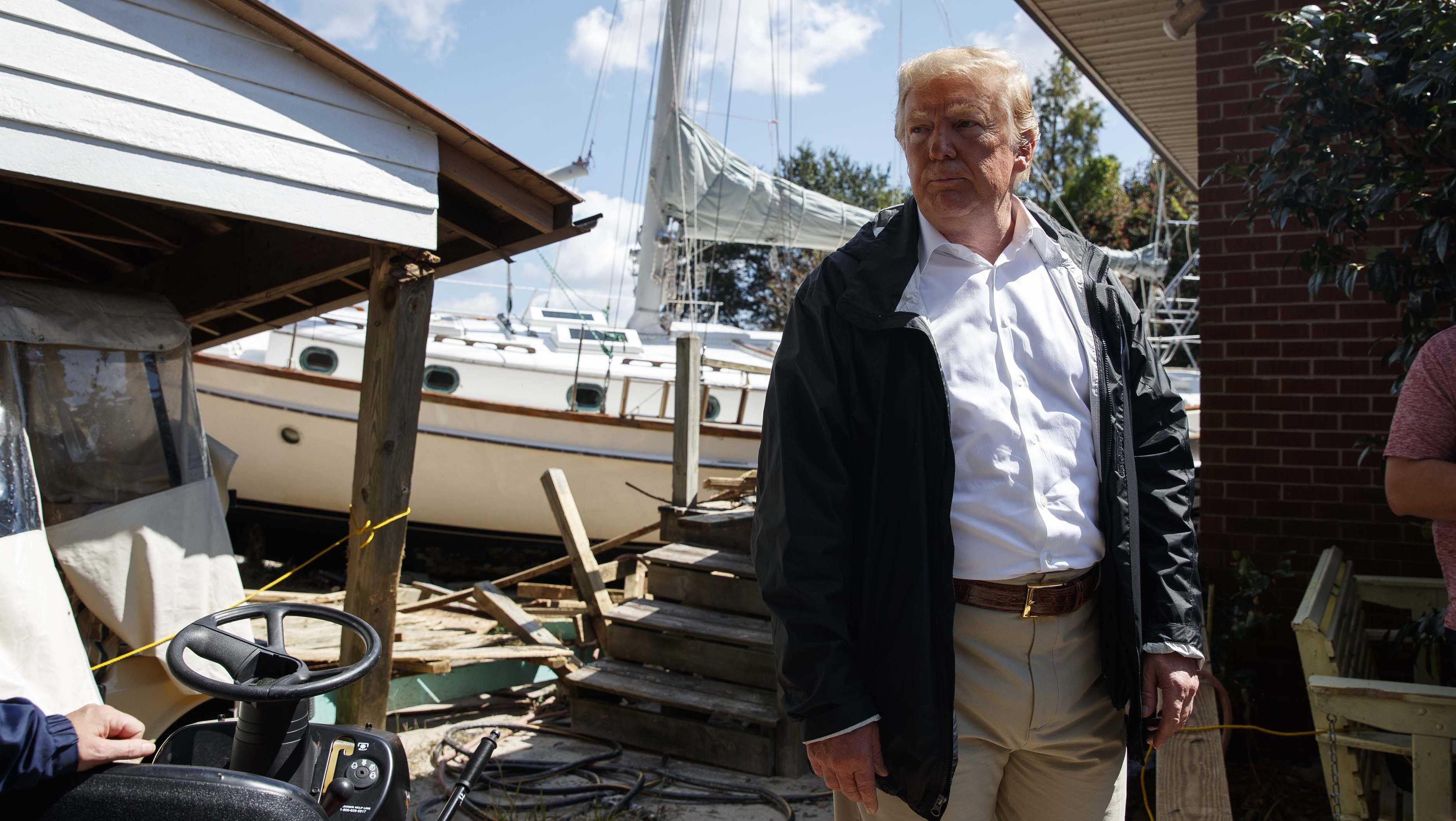President Donald Trump visits a house where a boat wash ashore in the backyard while touring a neighborhood impacted by Hurricane Florence, Wednesday, Sept. 19, 2018, in New Bern, N.C. (AP Photo/Evan Vucci)