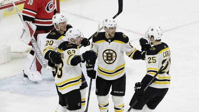 Boston Bruins' David Pastrnak (88), of the Czech Republic, is congratulated by Riley Nash (20), Brad Marchand (63) and Brandon Carlo (25) following Pastrnak's goal against Carolina Hurricanes goalie Cam Ward (30) during the third period of an NHL hockey game in Raleigh, N.C., Tuesday, March 13, 2018. Boston won 6-4.