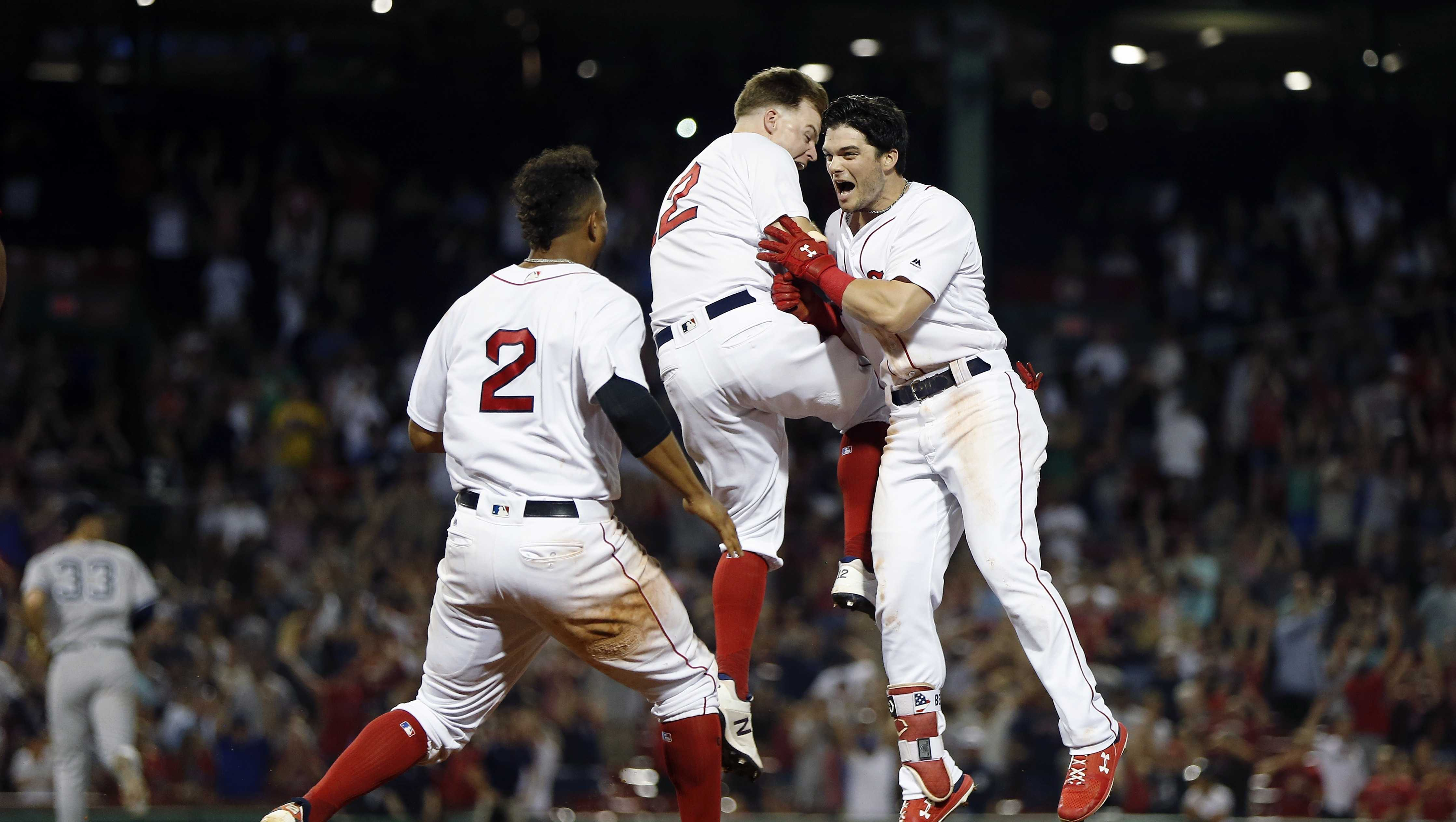 Boston Red Sox's Andrew Benintendi, right, celebrates his game-winning RBI single with Brock Holt, center, and Xander Bogaerts (2) during the tenth inning of a baseball game against the New York Yankees in Boston, Monday, Aug. 6, 2018.