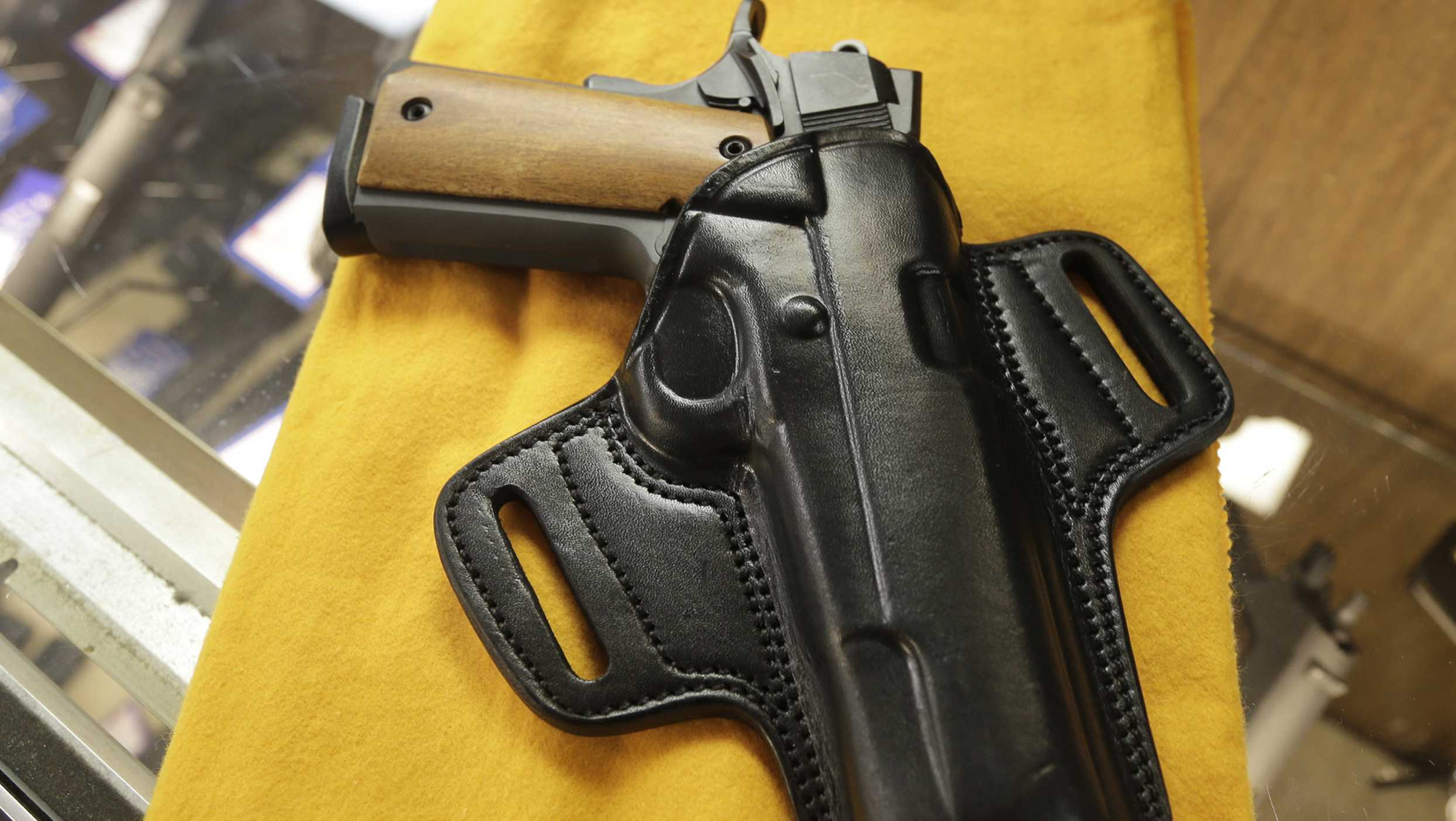 A semi-automatic handgun and a holster are displayed