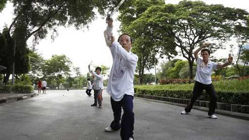 A Tai Chi sword instructor leads a group of students during an early morning practice session in Lumpini Park in Bangkok, Thailand, Thursday, Aug. 6, 2015. Urban oasis Lumpini Park lies in the heart of Bangkok's busy business district and can be packed with residents exercising in the early morning and evening.