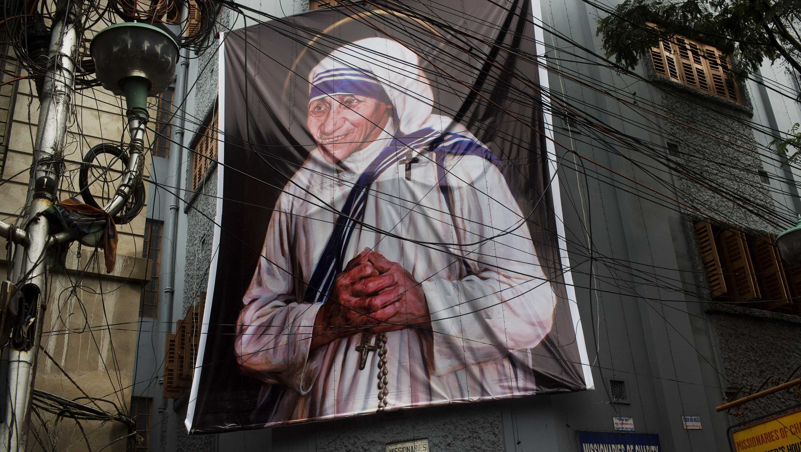 A giant picture of Mother Teresa is displayed outside the Missionaries of Charity Mother house in Kolkata, India, Saturday, Sept. 3, 2016. For many of the poor and destitute whom Mother Teresa served, the tiny nun was a living saint. Many at the Vatican would agree, but the Catholic Church nevertheless has a grueling process to make it official, involving volumes of historical research, the hunt for miracles and teams of experts to weigh the evidence. In Mother Teresa's case, the process will come to a formal end Sunday when Pope Francis declares the church's newest saint.
