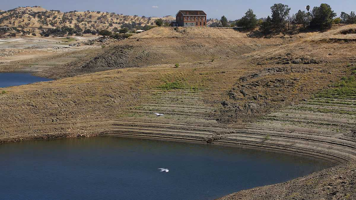In this Oct. 5, 2016, photo, the old Fresno County Superior Courthouse stands near a depleted water reservoir during a tour of the Millerton Lake area which feeds the San Joaquin River in Friant, Calif. A decade ago, environmentalists and the federal government agreed to revive a 150-mile stretch of California's second-longest river, an ambitious effort aimed at allowing salmon to again swim up to the Sierra Nevada foothills to spawn.