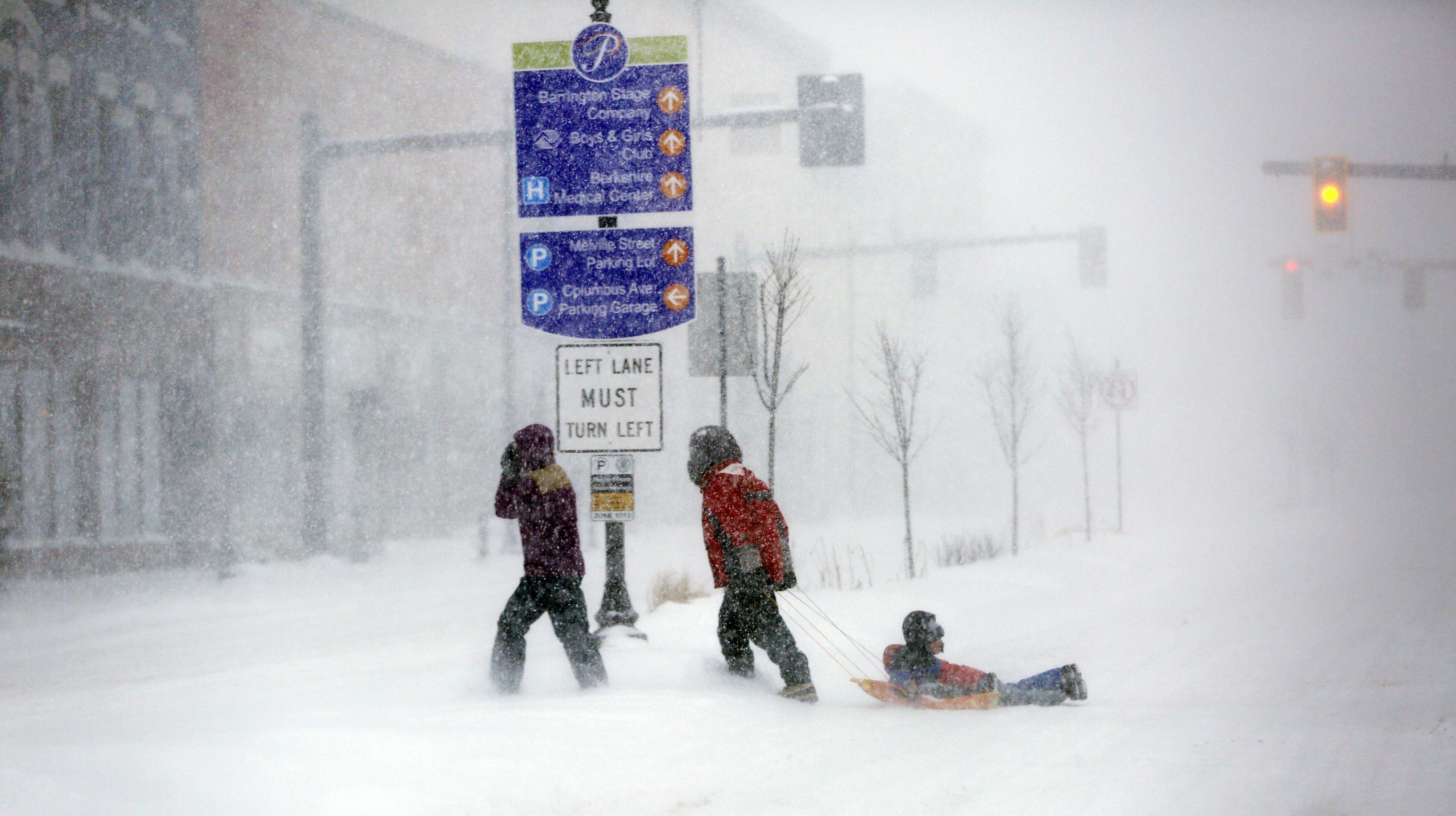 Walkers make their way through the snow-filled streets of Pittsfield, Mass., Tuesday, March 14, 2017.