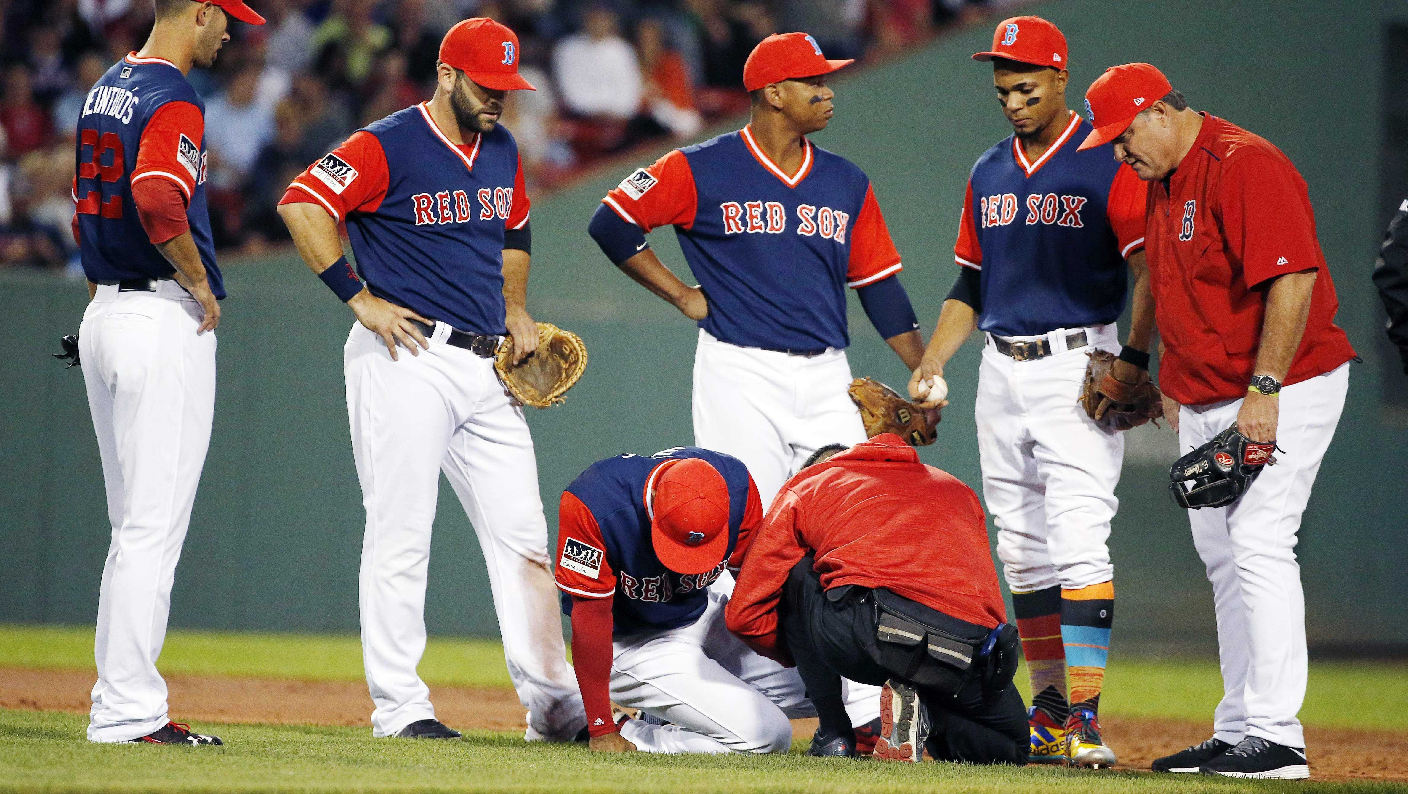 Boston Red Sox manager John Farrell, right, and players gather around Boston Red Sox's Eduardo Nunez, bottom left, after he was injured on a play during the second inning of a baseball game in Boston, Friday, Aug. 25, 2017.
